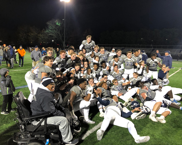 Football players on the ground celebrating championship