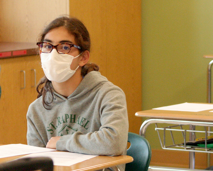 Student wearing mask and sitting in a classroom