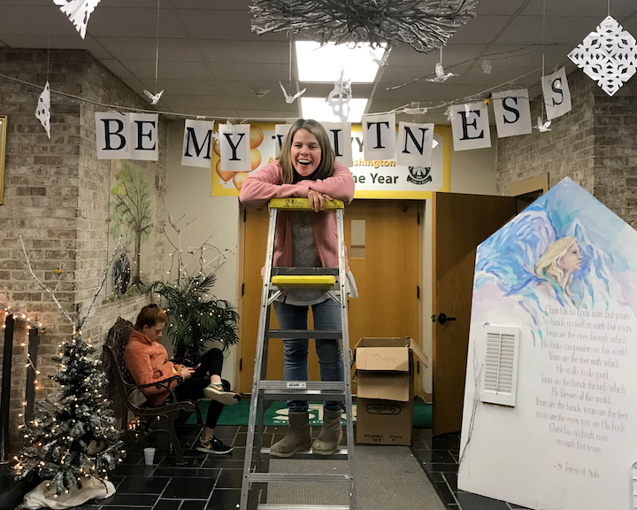 Ginger Browning on ladder while putting up decorations for CSW