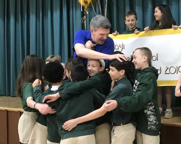 Nash surrounded by students hugging him
